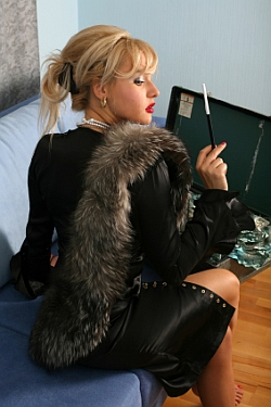Sexy blonde with cigarette, leather outfit, and fur stole